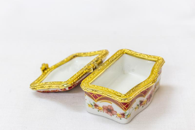 Το μικροσκοπικό ζωηρόχρωμο κιβώτιο κοσμημάτων με το χρυσό crimp σε ένα άσπρο υπόβαθρο Μακροεντολή με το εξαιρετικά ρηχό βάθος του στοκ φωτογραφία
