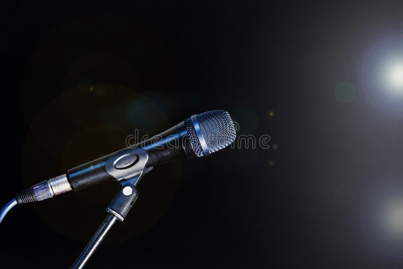 Το μικρόφωνο σε ένα τρίποδο στέκεται στο στάδιο αναμμένο από τα επίκεντρα μέσα στοκ φωτογραφία με δικαίωμα ελεύθερης χρήσης