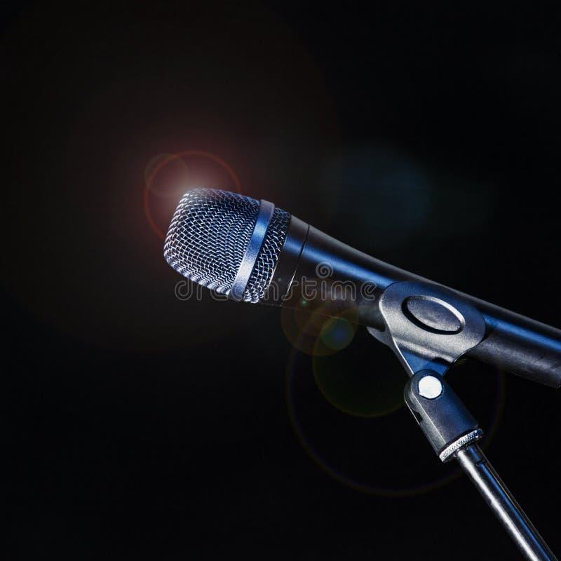 Το μικρόφωνο σε ένα τρίποδο στέκεται στο στάδιο αναμμένο από τα επίκεντρα μέσα στοκ εικόνες