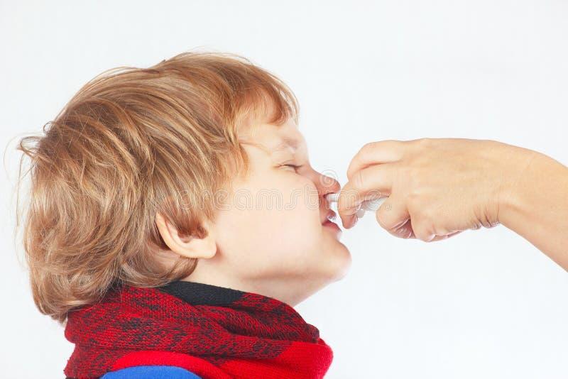 Το μικρό άρρωστο αγόρι χρησιμοποίησε τον ιατρικό ρινικό ψεκασμό στη μύτη στοκ φωτογραφία