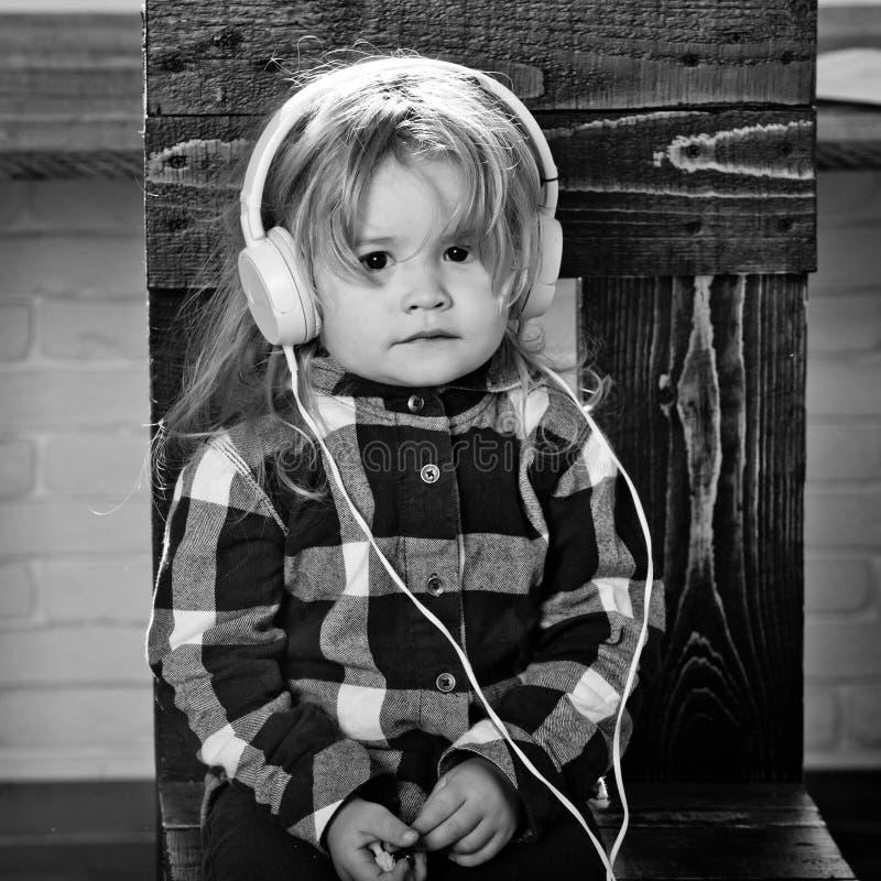 Το μικρό αγοράκι στην κάσκα ακούει μουσική ή audiobook στοκ εικόνα