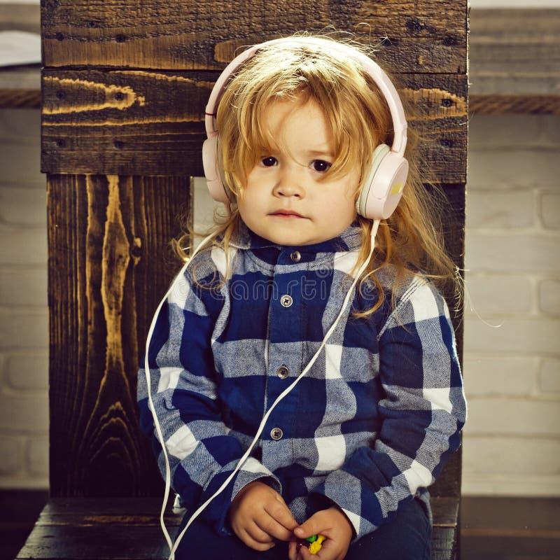 Το μικρό αγοράκι στην κάσκα ακούει μουσική ή audiobook στοκ φωτογραφία με δικαίωμα ελεύθερης χρήσης