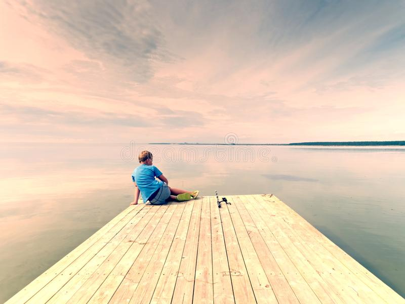 Το μικρό αγόρι αλιεύει στον ξύλινο τυφλοπόντικα στη θερινή ημέρα Παιδί ξανθών μαλλιών στην μπλε μπλούζα, γκρίζα ριγωτά σορτς στοκ εικόνες με δικαίωμα ελεύθερης χρήσης