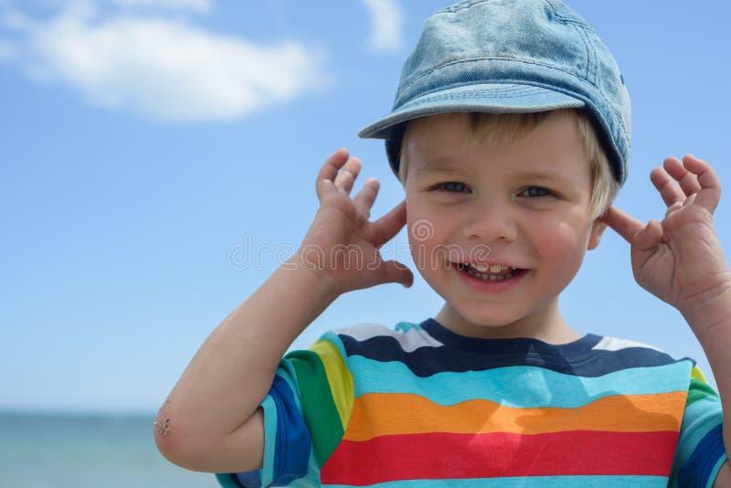 Το μικρό αγόρι κρατά τα χέρια του πέρα από τα αυτιά για να μην ακούσει στοκ εικόνα με δικαίωμα ελεύθερης χρήσης