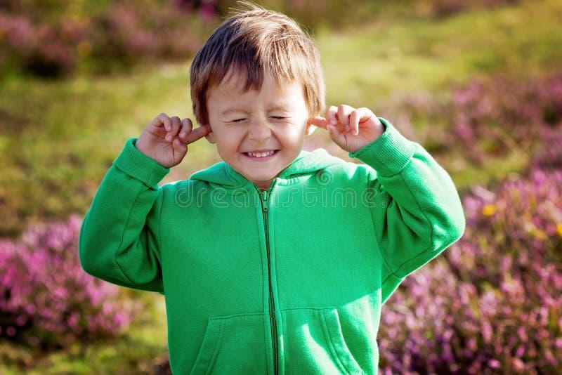 Το μικρό αγόρι κρατά τα χέρια του πέρα από τα αυτιά για να μην ακούσει στοκ εικόνες