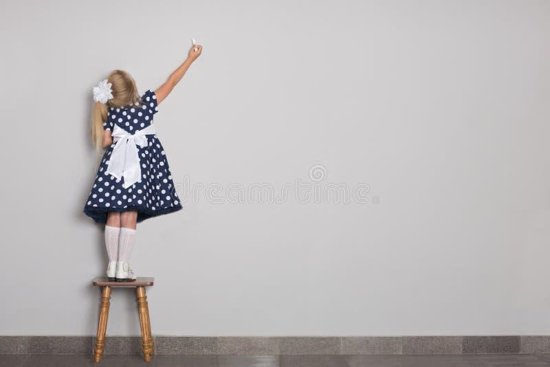 Το μικρό κορίτσι έγραψε στην κιμωλία σε έναν τοίχο στοκ εικόνες