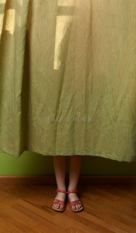 Το μικρό κορίτσι έκρυψε πίσω από την κουρτίνα στοκ φωτογραφία με δικαίωμα ελεύθερης χρήσης
