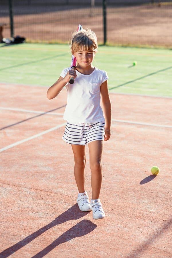 Το μικρό κορίτσι έντυσε άσπρο ομοιόμορφο με τη ρακέτα αντισφαίρισης στον ώμο περπατώντας στο υπαίθριο γήπεδο αντισφαίρισης στο ηλ στοκ εικόνες