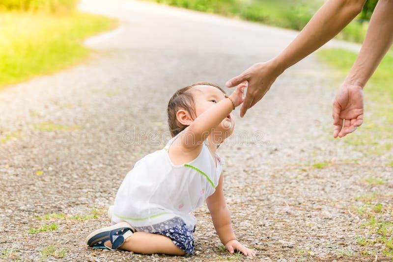 Το μικρό κορίτσι δίνει το χέρι στη μητέρα της Στάση μωρών βοηθειών MOM επάνω στοκ εικόνες