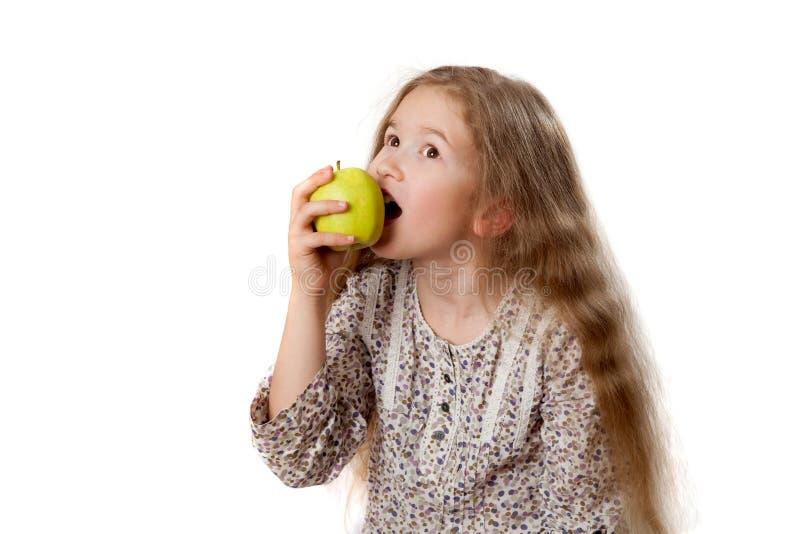 Το μικρό κορίτσι δαγκώνει το πράσινο μήλο στοκ φωτογραφία
