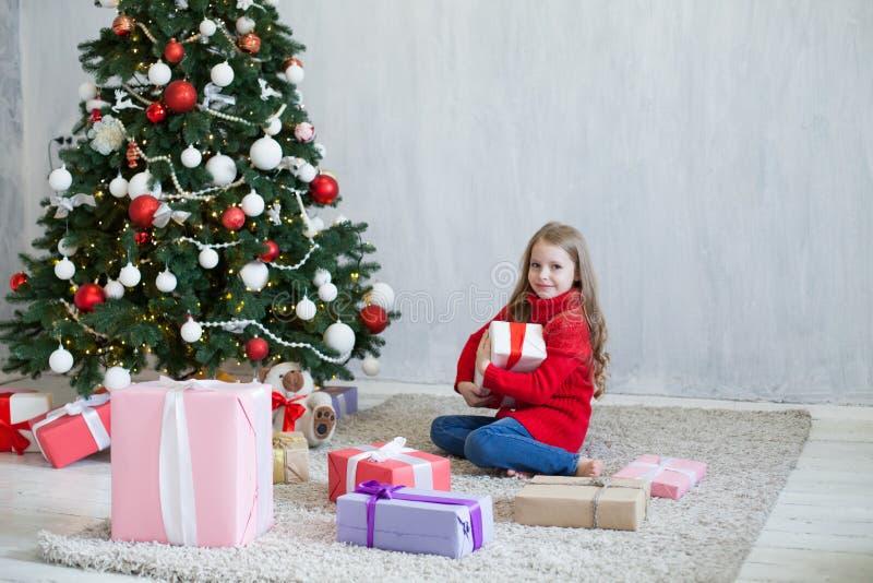 Το μικρό κορίτσι ανοίγει τη νέα διακόσμηση δέντρων έτους χριστουγεννιάτικων δώρων στοκ εικόνες με δικαίωμα ελεύθερης χρήσης