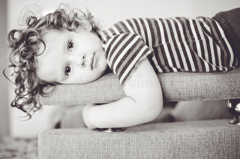 Το μικρό κορίτσι βάζει σε έναν καναπέ. στοκ φωτογραφίες