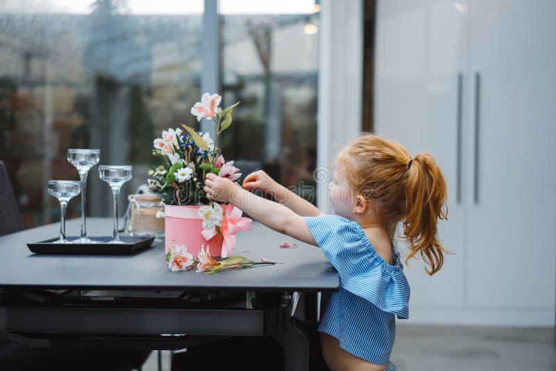 Το μικρό κορίτσι βάζει τα λουλούδια στον πίνακα στοκ εικόνες με δικαίωμα ελεύθερης χρήσης