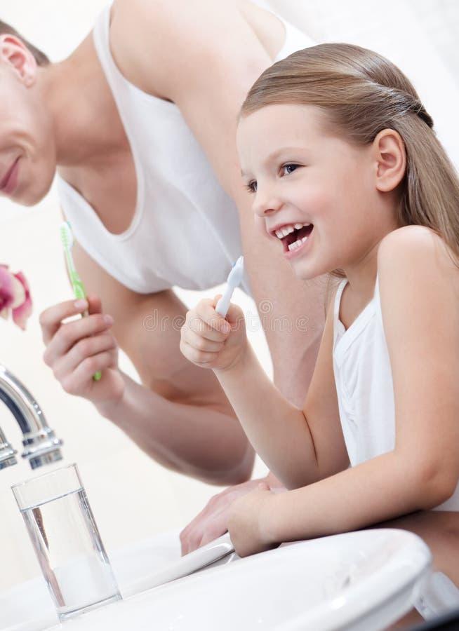 Το μικρό κορίτσι βουρτσίζει τα δόντια με τον πατέρα της στοκ φωτογραφίες
