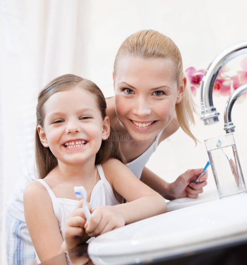Το μικρό κορίτσι βουρτσίζει τα δόντια με το mom της στοκ εικόνες