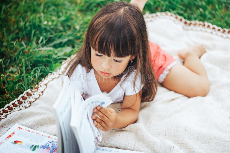 Το μικρό κορίτσι βρίσκεται στη χλόη και το βιβλίο ανάγνωσης στοκ εικόνες