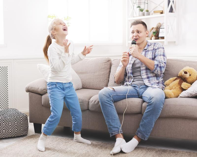 Το μικρό κορίτσι γελά του τραγουδιού πατέρων της στοκ εικόνες