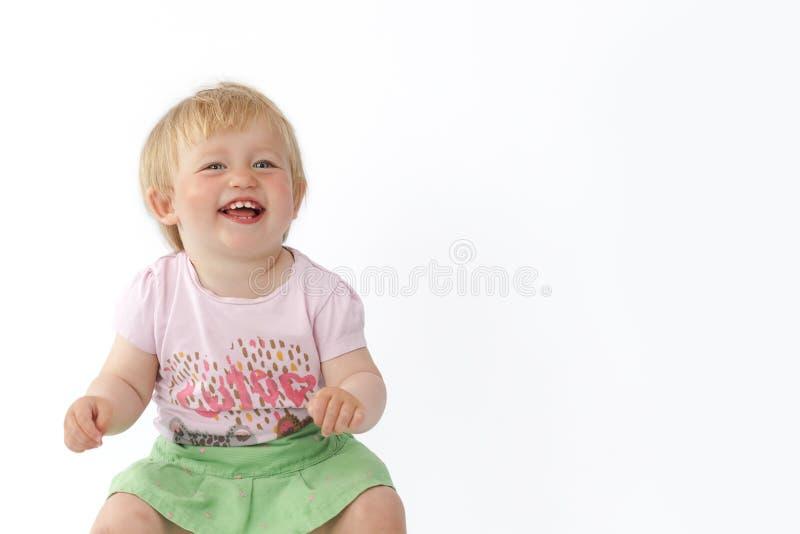 Το μικρό κορίτσι γελά και εξετάζει τη κάμερα στοκ εικόνα