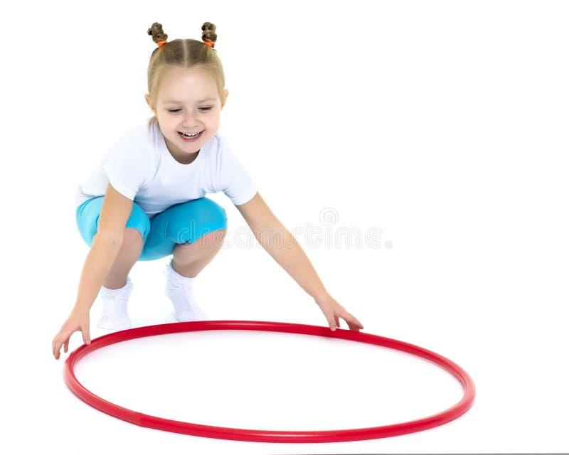 Το μικρό κορίτσι γυρίζει τη στεφάνη στοκ φωτογραφίες