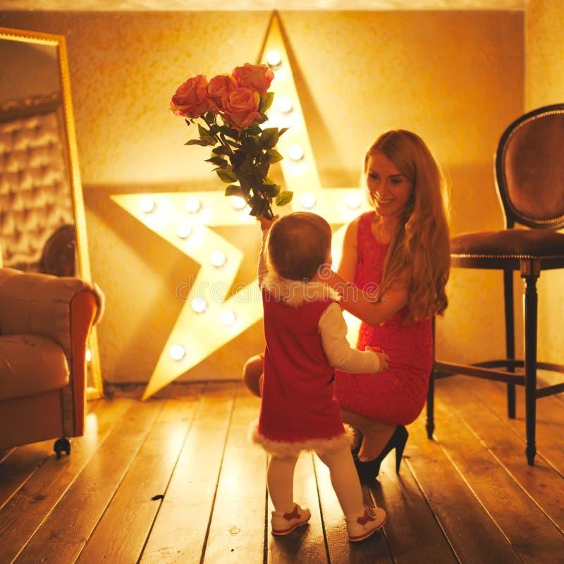 Το μικρό κορίτσι δίνει την ανθοδέσμη μητέρων τριαντάφυλλών της στοκ εικόνες