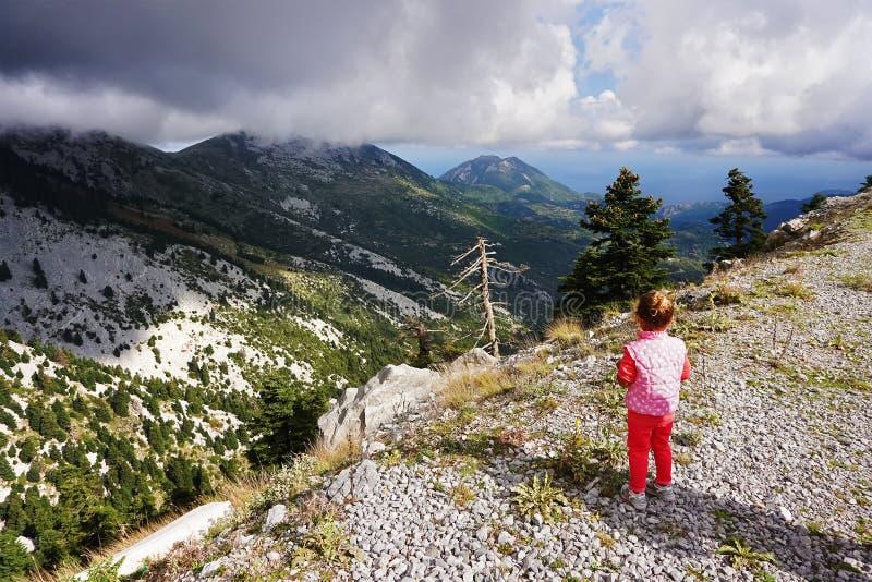 το μικρό κορίτσι εξετάζει τα βουνά στοκ εικόνες