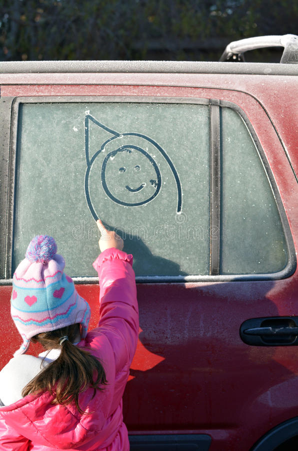 Το μικρό κορίτσι επισύρει την προσοχή ένα ευτυχές πρόσωπο σε ένα παγωμένο παράθυρο αυτοκινήτων στοκ εικόνα με δικαίωμα ελεύθερης χρήσης