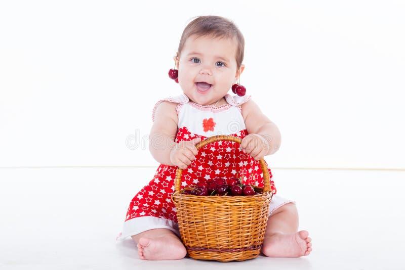 Το μικρό κορίτσι κάθεται με τα κεράσια καλαθιών στοκ φωτογραφίες