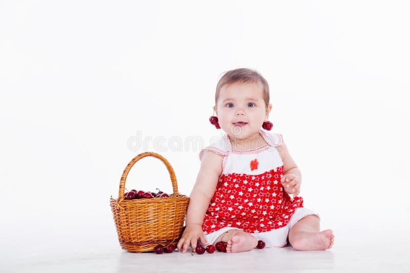 Το μικρό κορίτσι κάθεται με τα κεράσια καλαθιών στοκ εικόνες με δικαίωμα ελεύθερης χρήσης