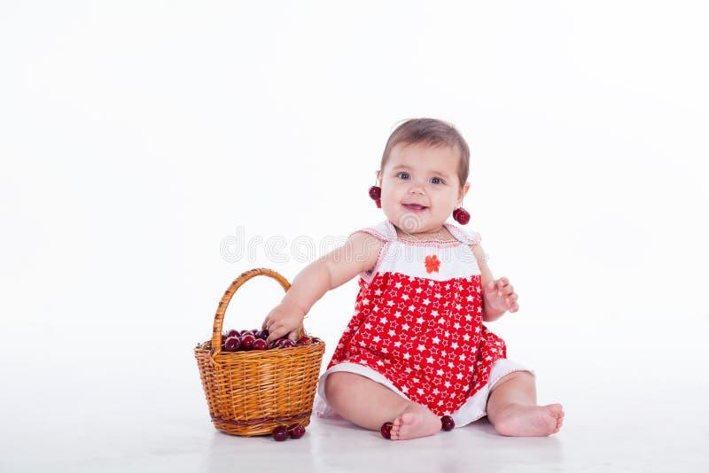 Το μικρό κορίτσι κάθεται με τα κεράσια καλαθιών στοκ εικόνες