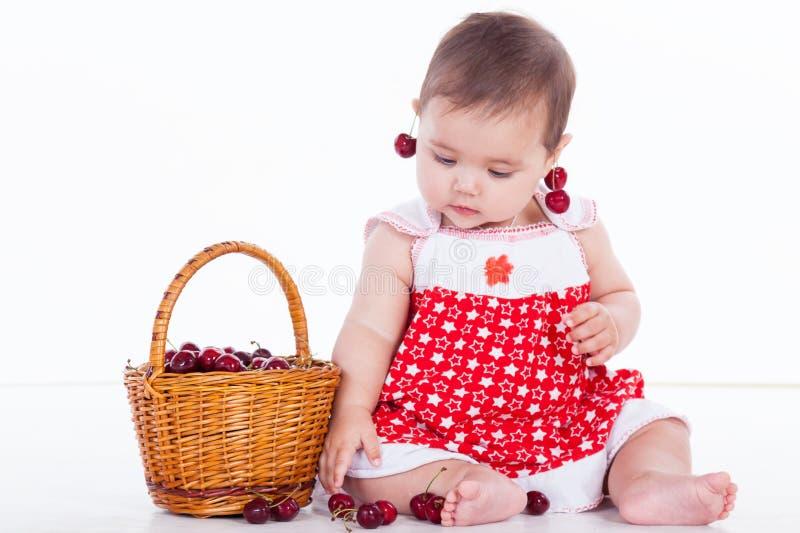 Το μικρό κορίτσι κάθεται με τα κεράσια καλαθιών στοκ εικόνα
