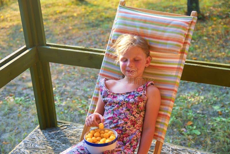 Το μικρό κορίτσι κάθεται σε έναν κήπο deckchair σε μια βεράντα Το μικρό κορίτσι τρώει το τυρί αρωμάτισε τα πρόχειρα φαγητά στοκ φωτογραφία με δικαίωμα ελεύθερης χρήσης