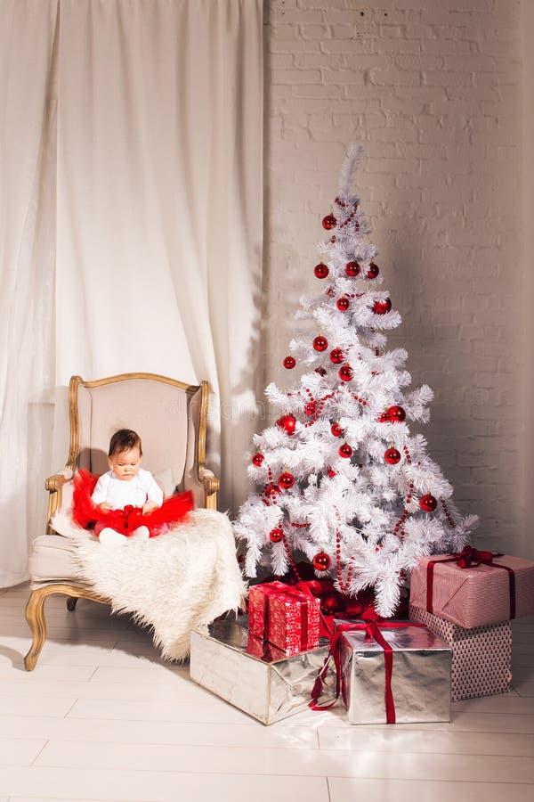 Το μικρό κορίτσι κάθεται σε μια καρέκλα κοντά στα Χριστούγεννα στοκ εικόνες με δικαίωμα ελεύθερης χρήσης