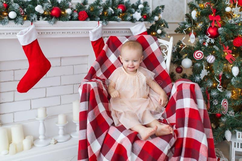 Το μικρό κορίτσι κάθεται σε μια καρέκλα κοντά στο χριστουγεννιάτικο δέντρο στοκ εικόνα με δικαίωμα ελεύθερης χρήσης