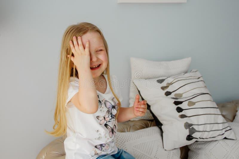 Το μικρό κορίτσι καλύπτει το πρόσωπό της με το χέρι Το μικρό κορίτσι καλύπτει το πρόσωπό της με ένα χέρι peekaboo Συγκινήσεις παι στοκ εικόνες