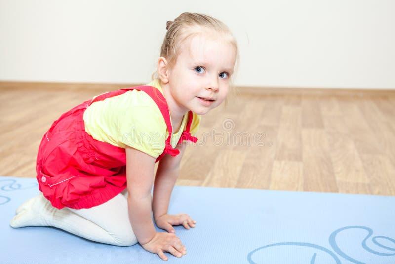 Το μικρό κορίτσι κατά τη διάρκεια των αθλητικών παιχνιδιών είναι στο χαλί στοκ εικόνα με δικαίωμα ελεύθερης χρήσης