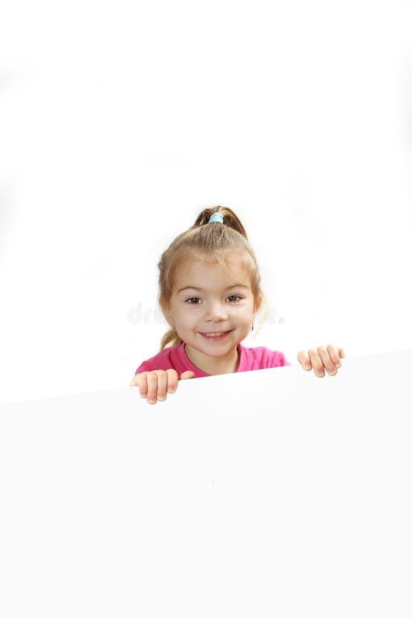 Το μικρό κορίτσι κοιτάζει έξω λόγω ενός φύλλου του εγγράφου στοκ φωτογραφίες