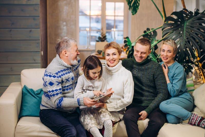 Το μικρό κορίτσι κρατά το λεύκωμα φωτογραφιών στα χέρια της ενώ οι συγγενείς της χαμογελούν στοκ εικόνες