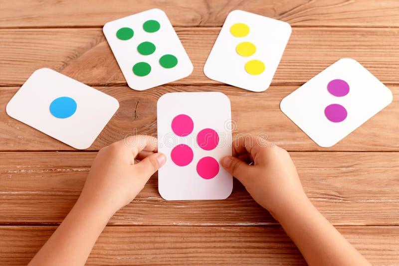 Το μικρό κορίτσι κρατά μια κάρτα λάμψης στα χέρια του και μαθαίνει το χρώμα, μορφή, ποσότητα Ζωηρόχρωμες κάρτες λάμψης για τα παι στοκ εικόνα με δικαίωμα ελεύθερης χρήσης