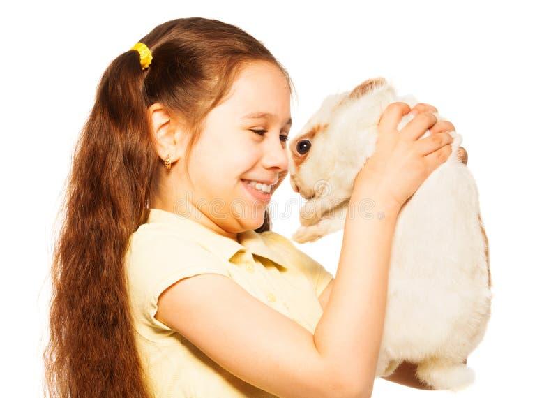 Το μικρό κορίτσι κρατά το στενό πορτρέτο κουνελιών στο λευκό στοκ εικόνα με δικαίωμα ελεύθερης χρήσης