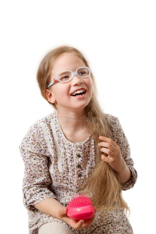 Το μικρό κορίτσι κτενίζει την τρίχα της στοκ φωτογραφίες