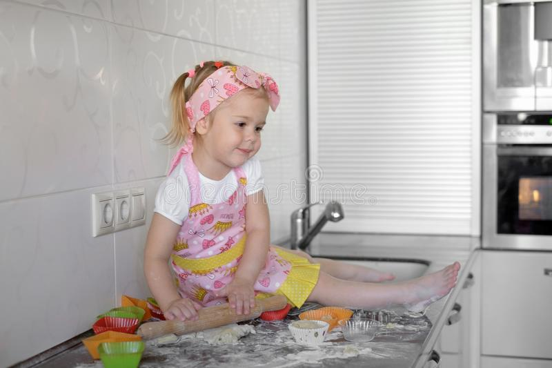 Το μικρό κορίτσι μαγειρεύει στην κουζίνα Κατοχή της διασκέδασης κατασκευάζοντας τα κέικ και τα μπισκότα στοκ εικόνες