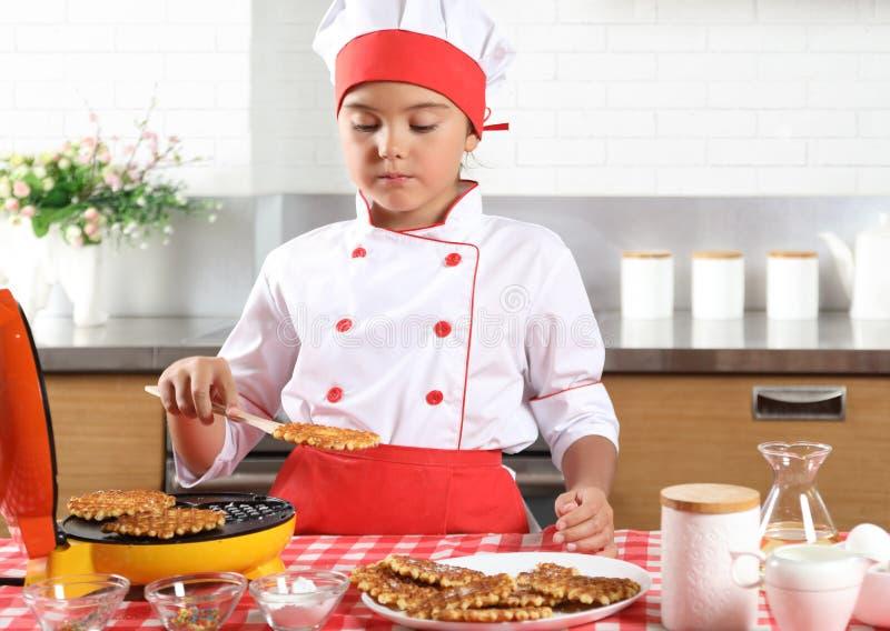 Το μικρό κορίτσι μαγειρεύει τις βάφλες στην κουζίνα στοκ εικόνες