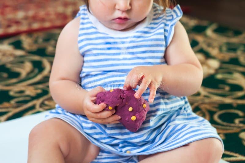 Το μικρό κορίτσι μαθαίνει να χρησιμοποιεί τη ζωηρόχρωμη ζύμη παιχνιδιού εσωτερική στοκ εικόνες