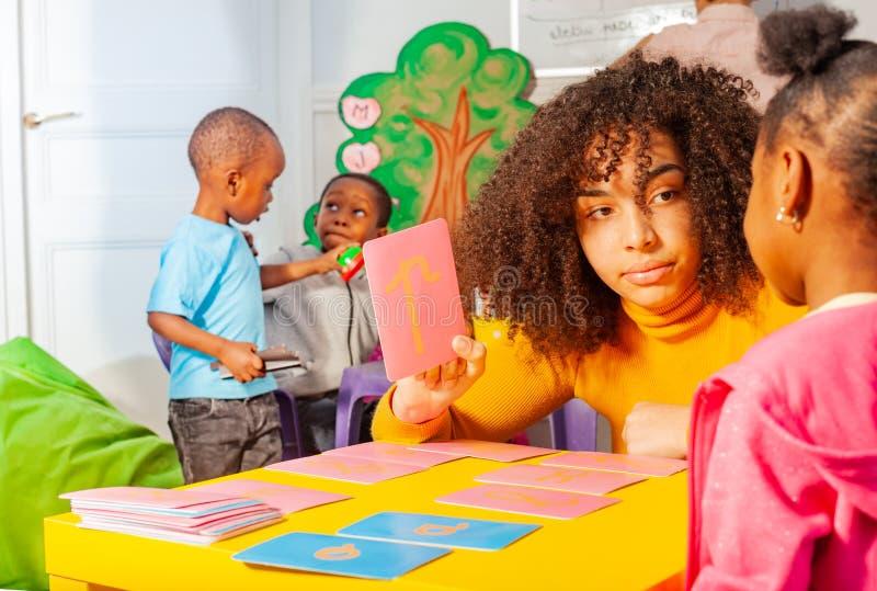 """Το μικρό κορίτσι μαθαίνει Ï""""Î¿ ρέον αλφάβητο, παιδικός σταθμός στοκ φωτογραφία με δικαίωμα ελεύθερης χρήσης"""