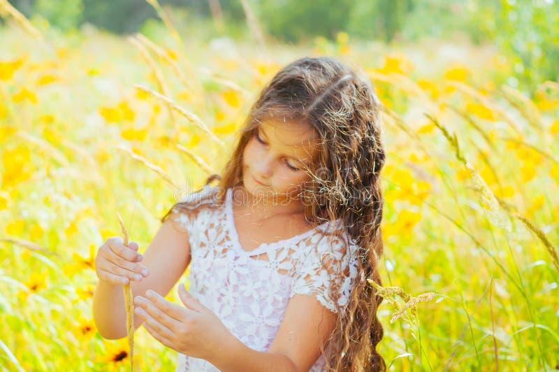 Το μικρό κορίτσι με μακρυμάλλη σε ένα άσπρο φόρεμα χαίρεται για έναν τομέα με τα λουλούδια στοκ φωτογραφία με δικαίωμα ελεύθερης χρήσης