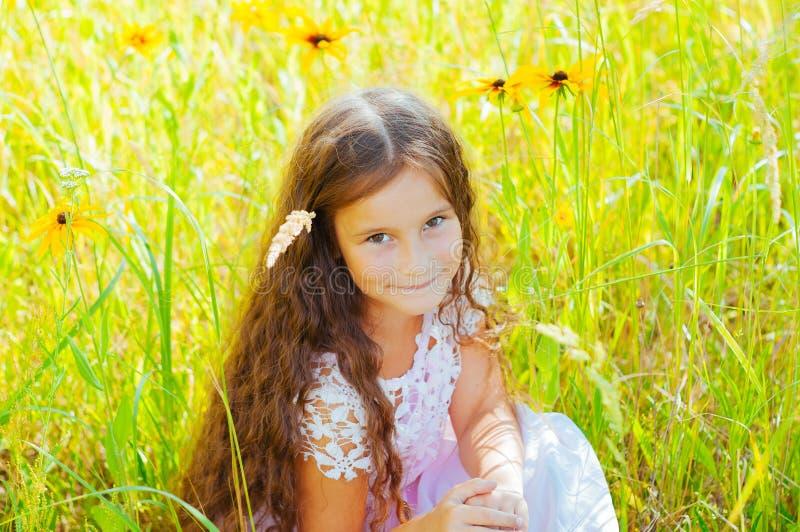Το μικρό κορίτσι με μακρυμάλλη σε ένα άσπρο φόρεμα χαίρεται για έναν τομέα με τα λουλούδια στοκ εικόνες με δικαίωμα ελεύθερης χρήσης