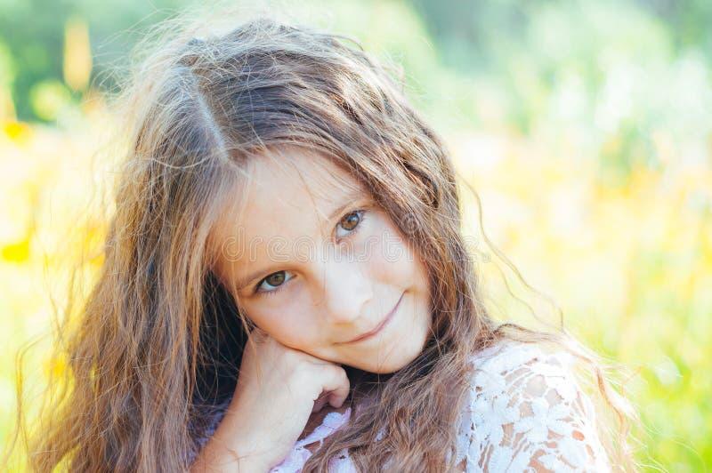 Το μικρό κορίτσι με μακρυμάλλη σε ένα άσπρο φόρεμα χαίρεται για έναν τομέα με τα λουλούδια στοκ εικόνα