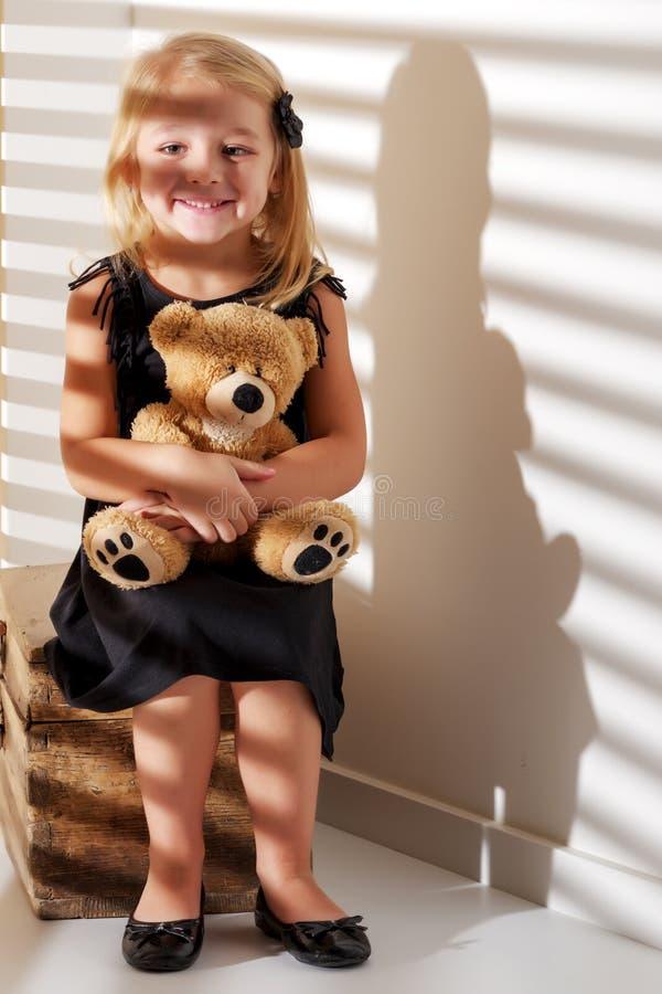 Το μικρό κορίτσι με μια teddy αρκούδα, που φωτίζεται από το φως από κερδίζει στοκ εικόνα