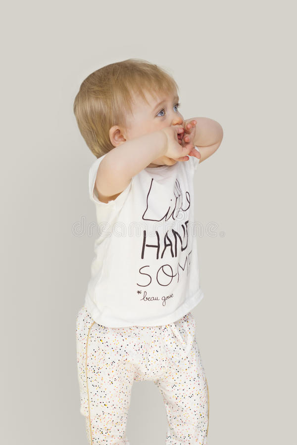 Το μικρό κορίτσι με τα μπλε μάτια σε ένα γκρίζο υπόβαθρο καλύπτει το πρόσωπό του με τα χέρια του στοκ εικόνες