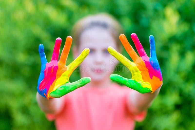Το μικρό κορίτσι με τα χέρια χρωμάτισε στα ζωηρόχρωμα χρώματα έτοιμα για τις τυπωμένες ύλες χεριών στοκ φωτογραφία με δικαίωμα ελεύθερης χρήσης